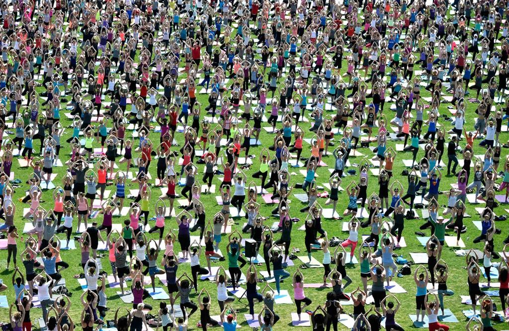 Multidão aproveita um dia ensolarado para uma sessão de ioga em Parliament Hill no Canadá. Bonito, não é?