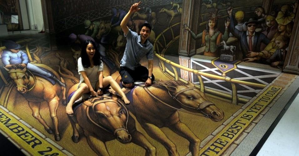 Visitantes interagem com uma pintura em três dimensões (3D) de Kurt Wenner, durante a exposição Artphoria (16/12/2013) na Indonésia.